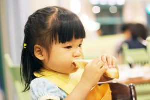 Chinese kid eating bread